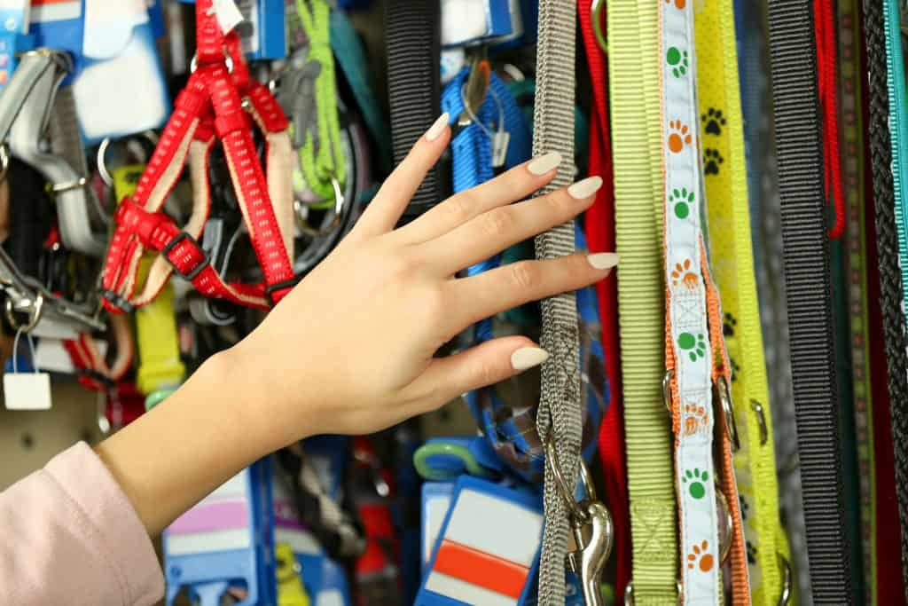 Lots of cat harnesses and leashes hanging from a display in a store. A woman's hand is seen browsing through them.