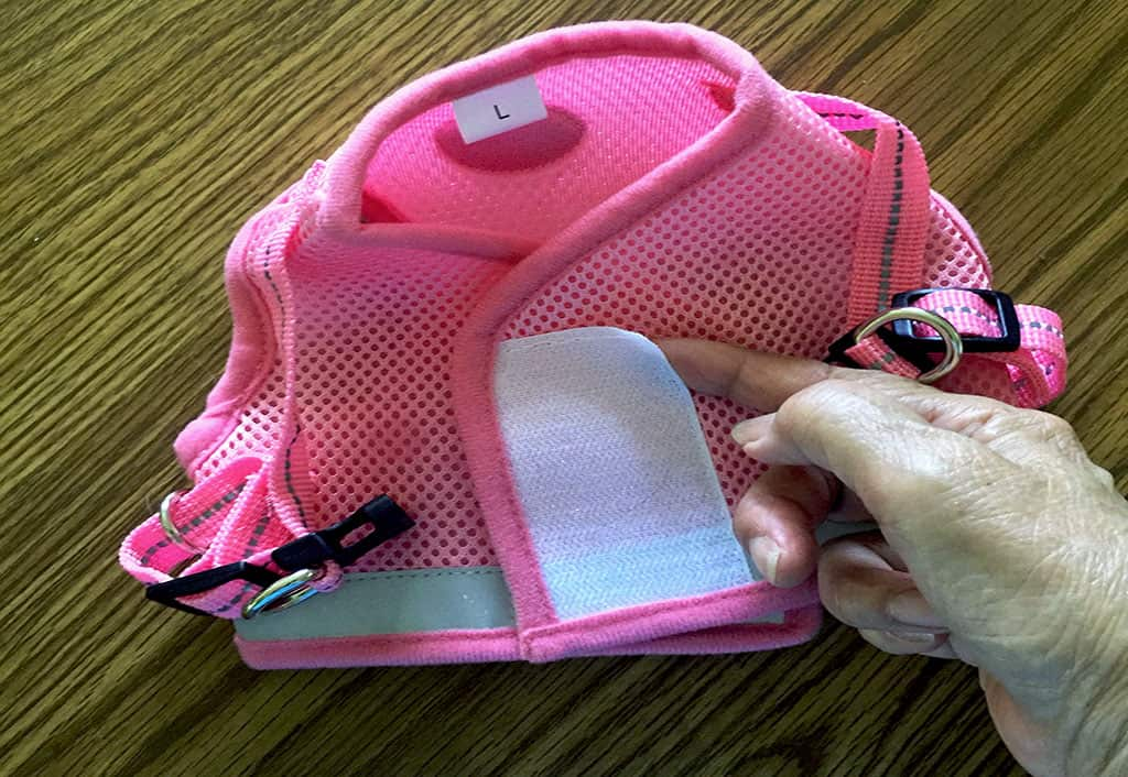 A picture of the Gauterf pink cat vest harness (back). A hand is pointing to the white Velcro patch that is coming off from its stitching.