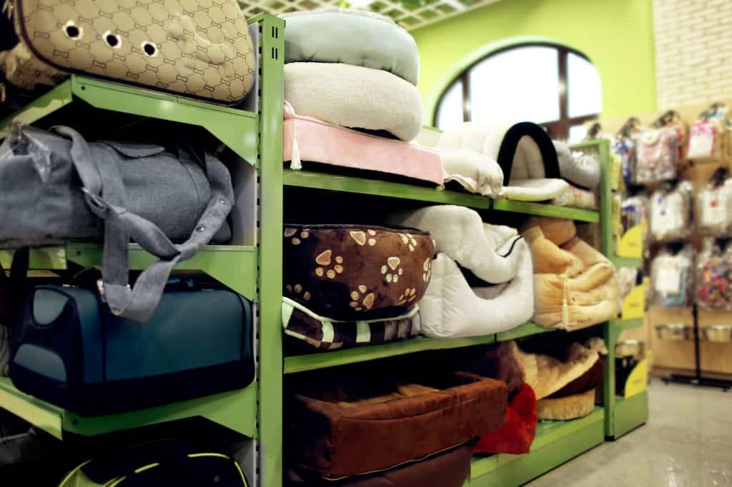A green shelf in a pet store that has 3 levels. There are different types of cat beds and cat carriers on each level of the shelf.