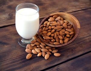 A glass cup filled with milk. To the right, a wooded bowl filled with almonds, some of which is spilled over onto the table and overlapping the base of the glass.