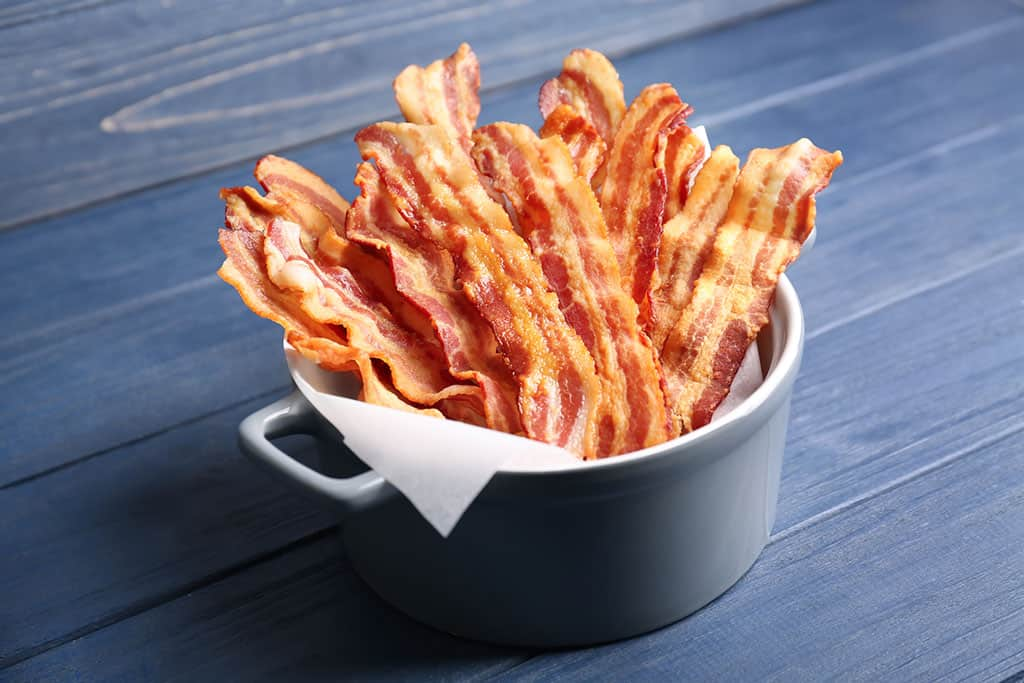 A grey pot lined with cloth or oven paper, filled with cooked bacon standing up vertically.