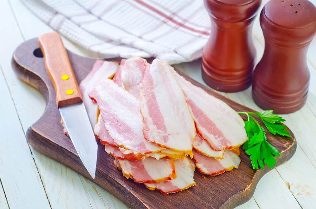 A brown, wooden cutting board with slices of raw bacon on it, along with a knife with a wooden handle and a piece of parsley on it. A white and red towel, wooden salt and pepper shakers can be seen off to the side.