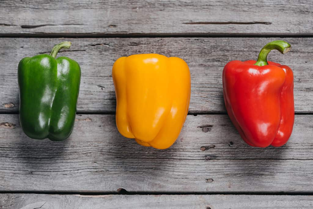 A green, yellow, and red bell pepper in a row displayed on top of a greyish wooden surface.