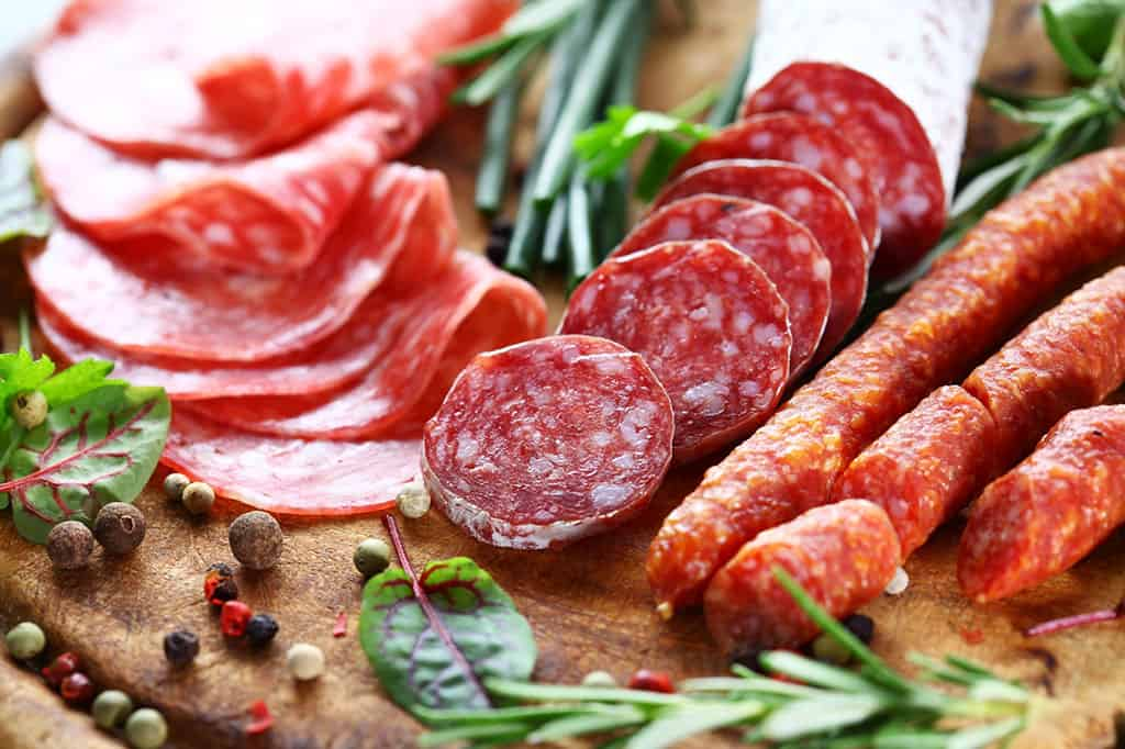A few different types of sausages, which are sliced and neatly displayed on a board with green herbs and peppercorns.