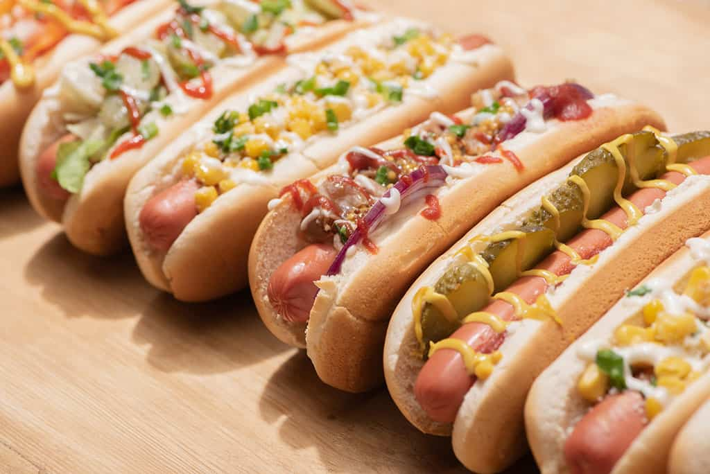 A line of hotdogs in a bun (6) placed next to each other. Each hot dog has a different topping that ranges from pickles, ketchup, corn, vegetables to other types of condiments (yellow and white).