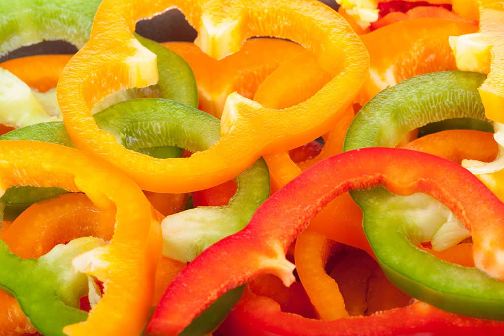 Thin slices of yellow, red, and green bell peppers stacked on top of each other.