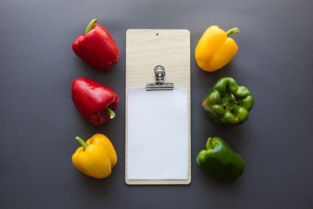Two of each color of bell peppers (red, yellow, and green) arranged neatly around a clipboard with a blank piece of white paper clipped to it. The background (surface) is grey.