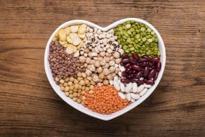 A white, heart-shaped bowl filled with different types of beans, ranging from white, orange, brown, green, and yellow beans.