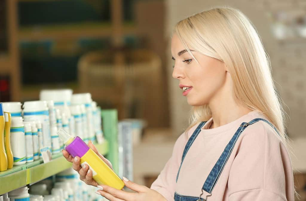 A young, blonde woman holding and inquisitively looking at a bottle that looks like pet shampoo. She is in a store and in front a shelf with a row of products in front of her.