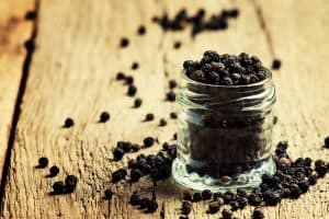 A glass bottle full of black peppercorns, with some spilling over next to the bottle and scatter all over the wooden tabletop.