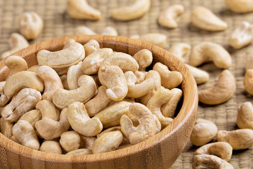 A brown wooden bowl filled with cashews. Cashews can also be seen scattered around the bowl.