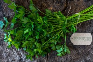 """A bunch of parsley on top of a wooden surface which looks like the inside of a tree trunk. There is a tag attached to the bunch of parsley that reads, """"PARSLEY."""""""
