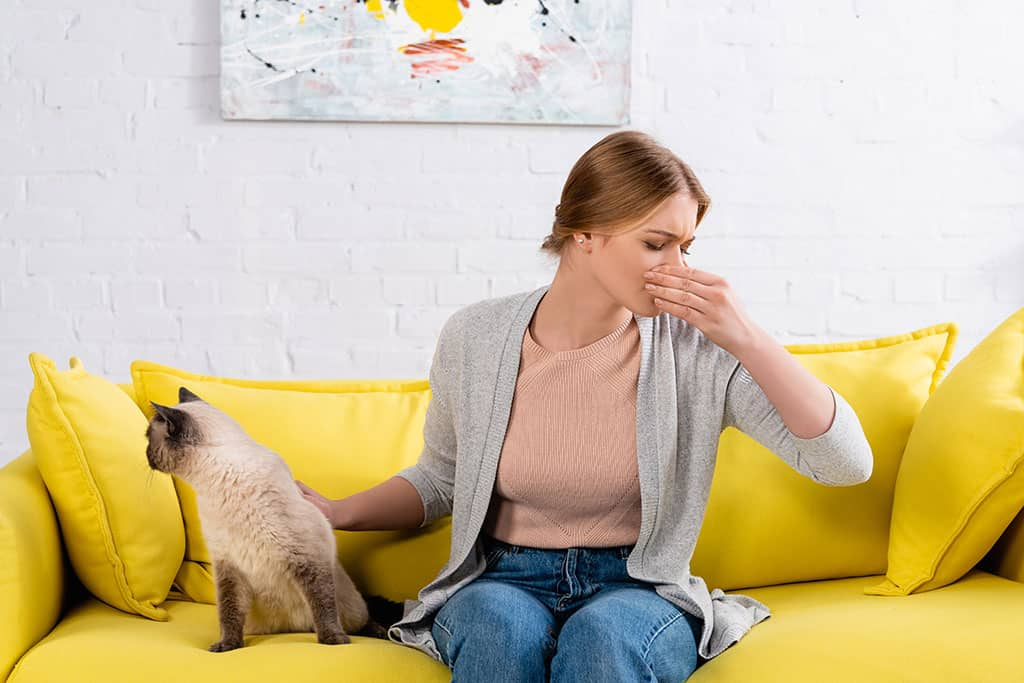 A woman covering her mouth and nose with her hand while sitting down on a sofa, with a cat next to her.