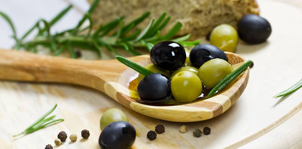 A wooden spoon resting on a wooden surface. There are green and black olives in the spoon, with other olives, peppercorns, and a sprig of rosemary around the spoon.