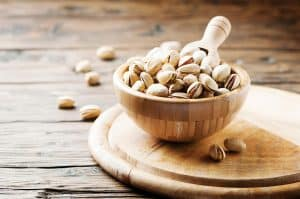 A wooden bowl that is filled with shelled pistachios that is resting on a wooden serving tray. There is a wooden scoop in the bowl of pistachios and some loose pistachios scattered around the bowl and on the table.