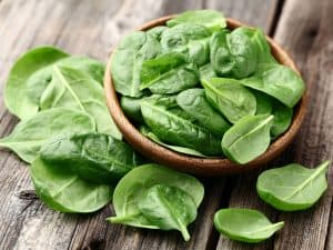 A wooden bowl full of spinach leaves that is on top of a wooden surface. There are also spinach leaves around the bowl on the table.
